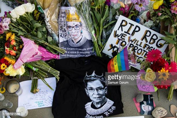 Mourners place flowers, messages, and mementos at a makeshift memorial in honor of Supreme Court Justice Ruth Bader Ginsburg in front of the US...