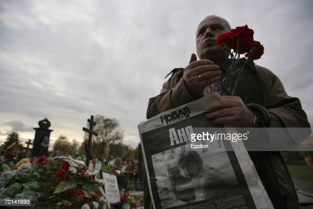 Mourners place flowers on the grave of Russian journalist Anna Politkovskaya who was buried in Troekurovskoe Cemetery on October 10 2006 in Moscow...