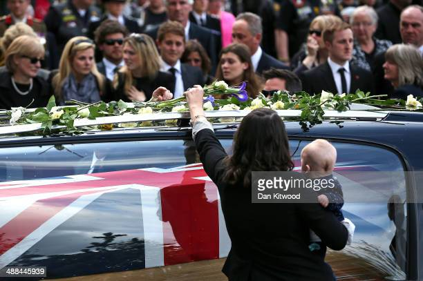 Mourners place flowers on the top of a hearse as the cortege passes by following the repatriation of five British servicemen who were killed in a...