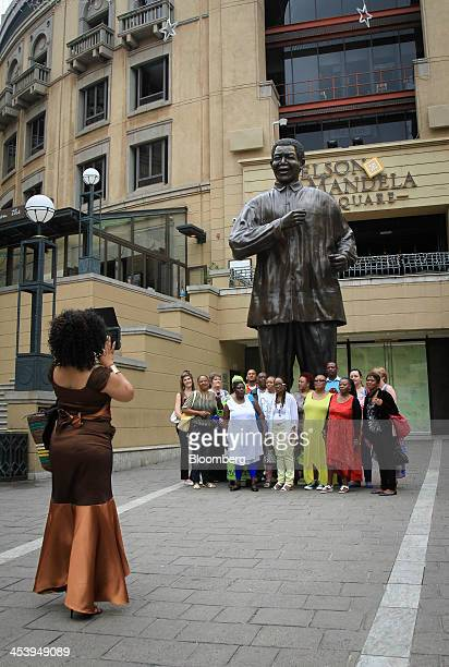Mourners pose for a photograph beside a statue of the former South African President Nelson Mandela on Nelson Mandela Square following the...
