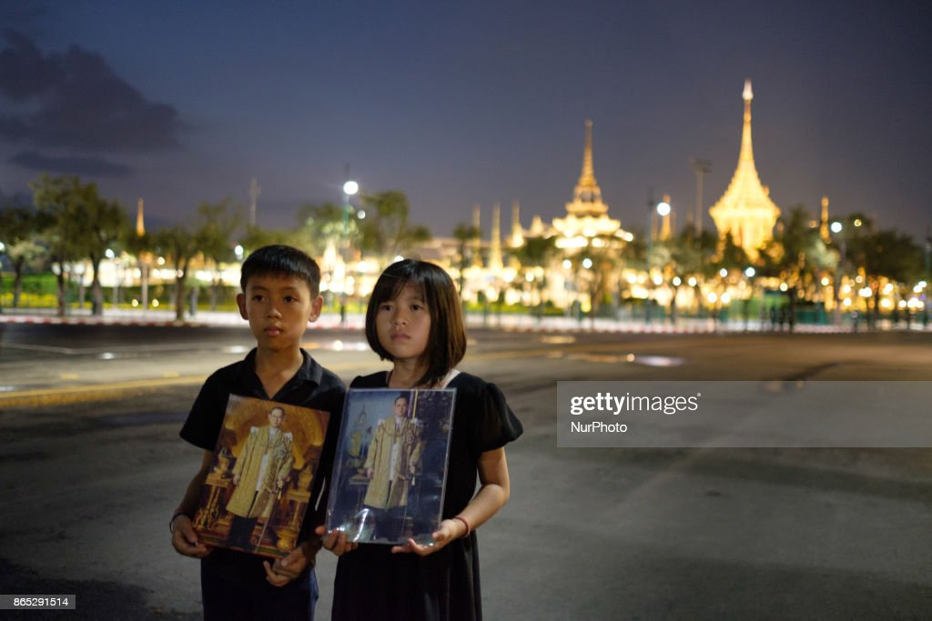 Mourners pose with pictures of the late Thai King Bhumiphol Adulyadej in front of the Royal Crematorium in Bangkok on October 22 2017