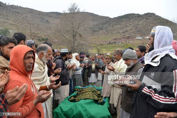 Mourners pray as they pay their respect to a 33yearold woman killed by a mortar shelling at Chhajla village in Mendhar near the Line of Control...