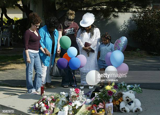 Mourners pray at the memorial in front of the house March 13 2004 in Fresno California According to reports nine bodies were found entwined in piles...