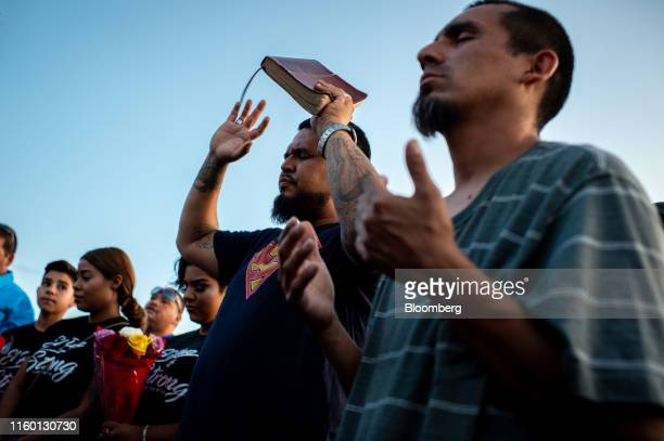 Mourners pray during a vigil outside a Walmart Inc. Retail store following a mass shooting in El Paso, Texas, U.S., on Tuesday, Aug. 6, 2019....