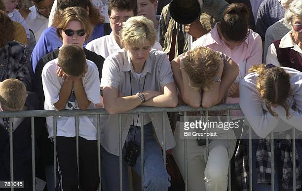 Mourners pray for the late Missouri Governor Mel Carnahan October 20 2000 during a memorial service on the steps of the Missouri state capitol in...