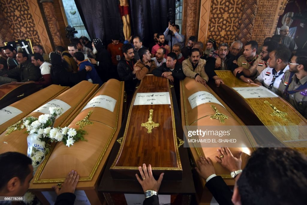 Mourners pray next to coffins of the victims of the blast at the Coptic Christian Saint Mark's church in Alexandria the previous day during a funeral procession at the Monastery of Marmina in the city of Borg El-Arab, east of Alexandria on April 10, 2017. Egypt prepared to impose a state of emergency after jihadist bombings killed dozens at two churches in the deadliest attacks in recent memory on the country's Coptic Christian minority. /