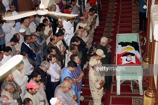 Mourners pray next to the coffin of Army officer Mustafa elWetedi one of the four Egyptian soldiers who were killed the day before by a roadside bomb...