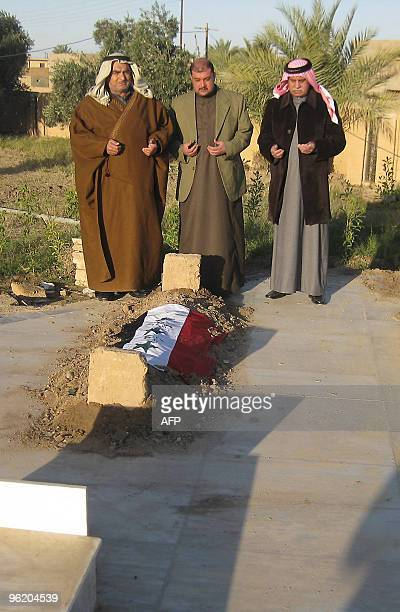 Mourners pray on January 27 2010 over the fresh grave of 'Chemical Ali' the notorious cousin and henchman of Saddam Hussein who was executed two days...