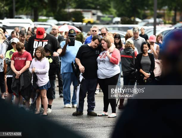 Mourners pray on June 1 for the victims of the mass shooting, during an improvised vigil in a parking lot of a shopping center in Virginia, Beach,...