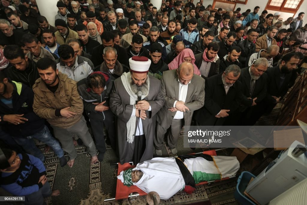 Mourners pray over the body of Abdullah Zeidan, a 33-year-old fisherman, during his funeral in Gaza City on January 13, 2018. A fisherman from the Gaza Strip was shot dead by the Egyptian army overnight for unclear reasons, Palestinian officials said Saturday, calling for an immediate investigation into the incident. /
