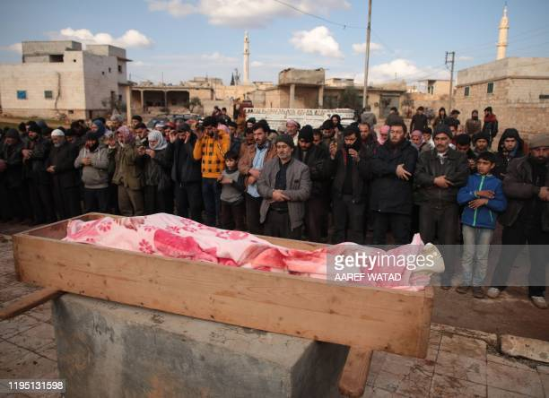 Mourners pray over the coffin of man killed after a reported proregime bombardment during his funeral in the village of Kafr Taal in Aleppo's western...