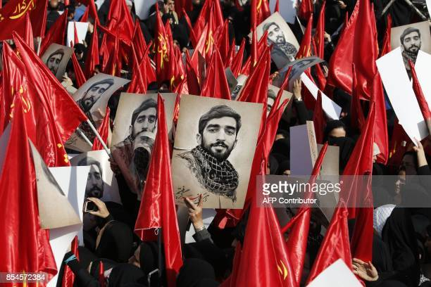 TOPSHOT Mourners raise portraits of Mohsen Hojaji a young member of Iran's elite revolutionary guards Corps who was beheaded in Syria by Islamic...