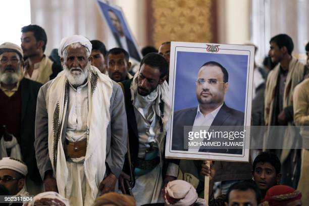 Mourners raise the portrait of slain Huthi leader Saleh alSamad and his six body guards during his funeral at a mosque in the Yemeni capital Sanaa on...