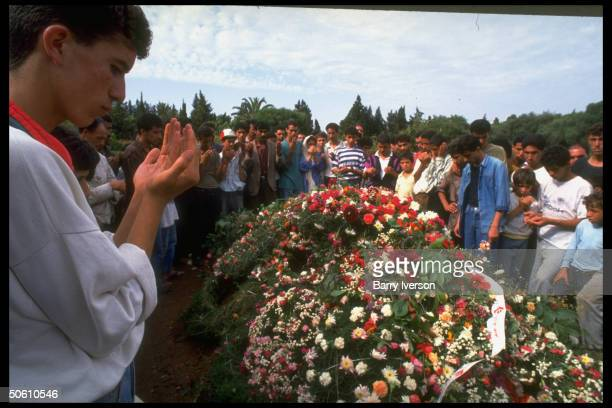 Mourners raising hands in show of respect ringing flowertopped grave of assassinated Pres Mohammed Boudiaf at cemetery in Algiers Algeria