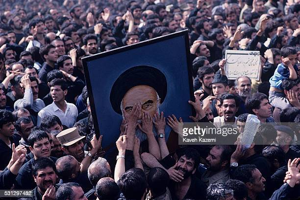 Mourners reach out to touch a portrait of Ayatollah Khomeini following his death Tehran Iran June 5 1989