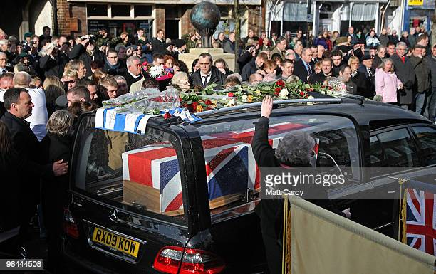Mourners react as the hearse carrying the body of Corporal Liam Riley leads that of Lance Corporal Graham Shaw along the High Street on February 5...
