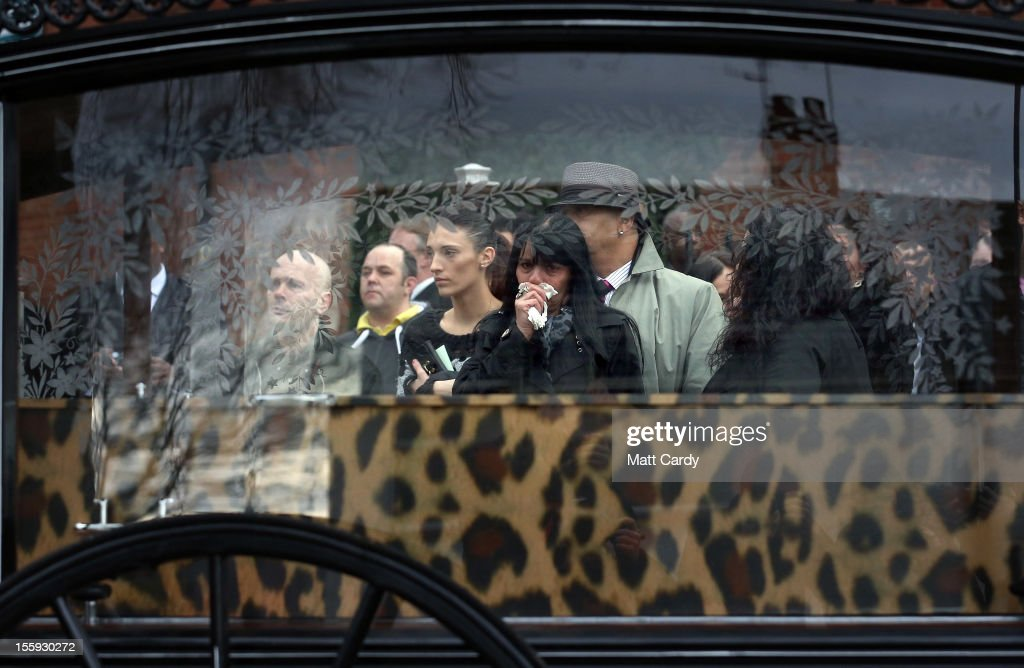 Mourners react as the horse drawn hearse carrying the leopard skin covered coffin of Karina Menzies arrives at the Church of the Resurrection for her funeral service on November 9, 2012 in Cardiff, Wales. Mother of three, Karina Menzies, 31, died during a series of hit and run collisions, which also injured 14 others in west Cardiff in October. A Cardiff man is currently facing murder and other charges.