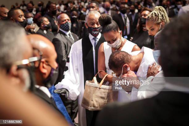 Mourners react as they look at the casket as the extended family processes into the private funeral for George Floyd at The Fountain of Praise church...