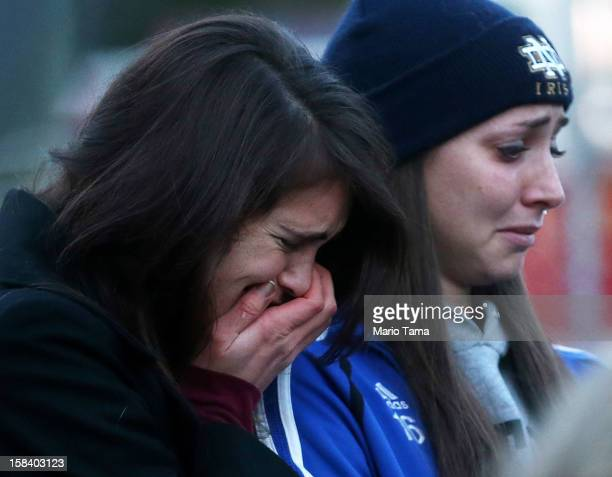 Mourners react at a makeshift memorial near the school following the mass shooting at Sandy Hook Elementary School on December 15 2012 in Newtown...