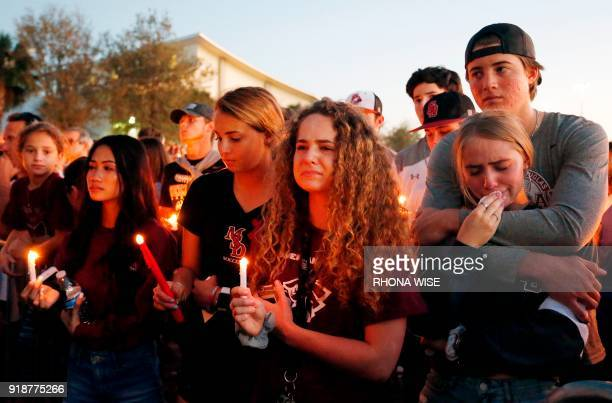 Mourners react during a candlelight vigil for the victims of Marjory Stoneman Douglas High School shooting in Parkland Florida on February 15 2018 A...