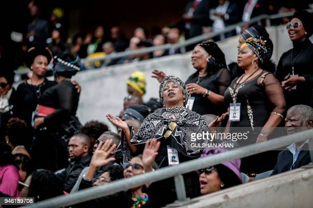 Mourners react from the stands of the full 37,500-seater Orlando Stadium in the township of Soweto during the funeral of the late anti-apartheid...