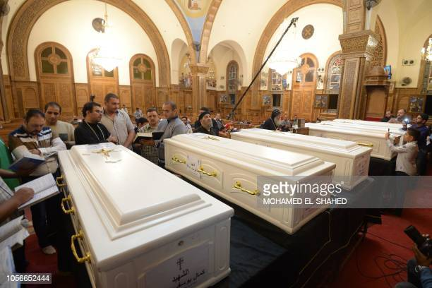 Mourners recite prayers over the coffins of victims killed in an attack a day earlier, during an early morning ceremony at the Prince Tadros church...