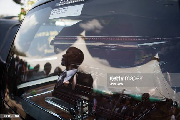 Mourners reflect on a hearse window as the coffin of President Uhuru Kenyatta's nephew Mbugua Mwangi is loaded in it after a funeral service for him...