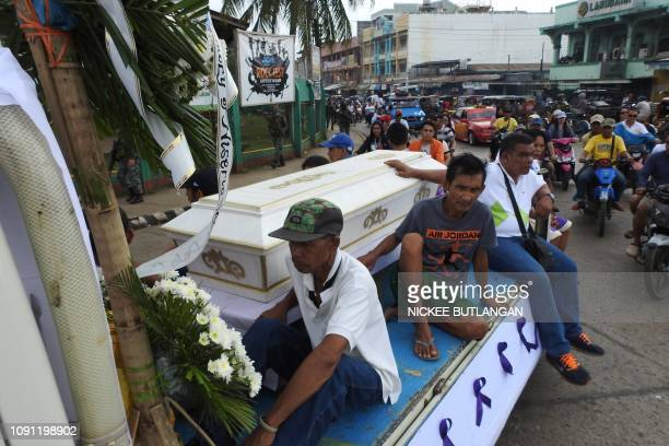 Mourners ride on a hearse during the funeral procession of a victim killed in the January 27 cathedral bombing in Jolo Sulu province on the southern...