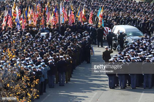 Mourners salute as the hearse carrying the remains of Detective Sean Suiter passes by on November 29 2017 in Baltimore Maryland Suiter a detective in...
