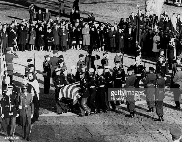Mourners salute the casket bearing the body of John F Kennedy as it is brought into Arlington National Cemetery