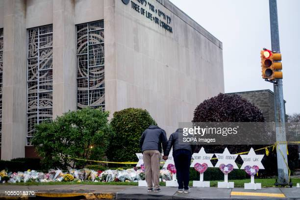 Mourners seen praying in front of the makeshift memorial at the site of the mass shooting After the tragic shooting in Pittsburgh PA at the Tree of...