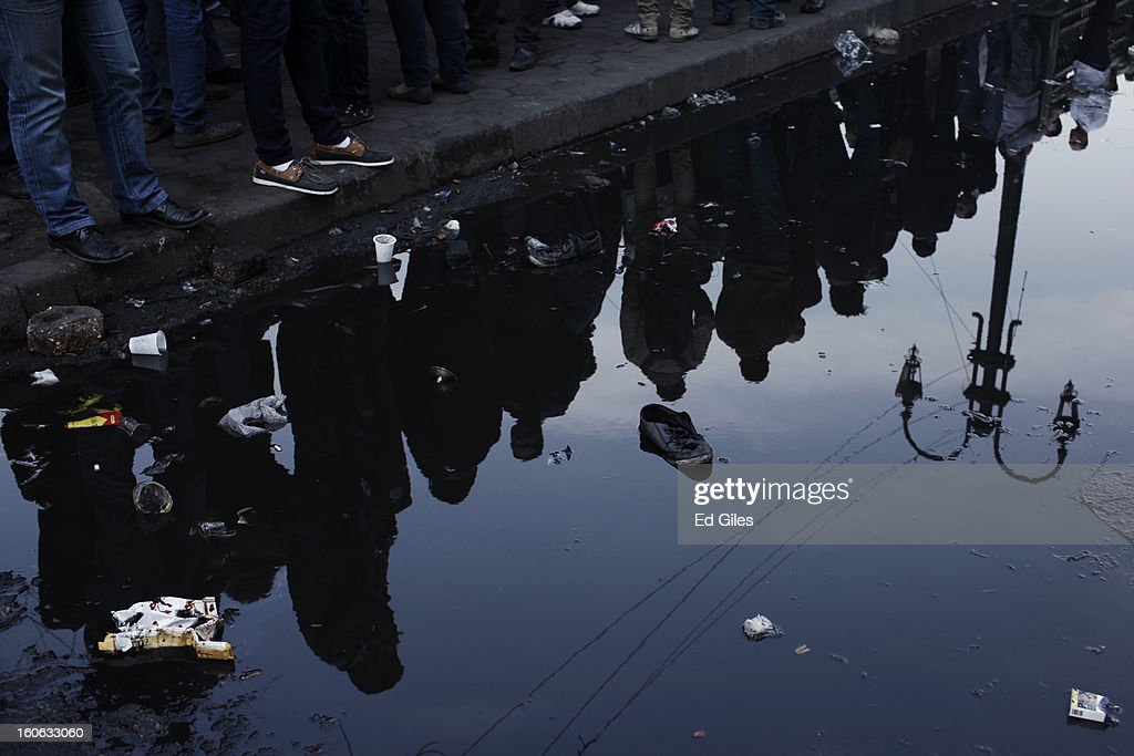 Mourners, seen reflected in a pool of water, attend a funeral for two protesters killed during violent clashes with Egyptian security forces in the Egyptian capital in previous days, at the Omar Makram Mosque in Tahrir Square, on February 4, 2013 in Cairo, Egypt. The funeral, held for Egyptian protesters Mohammed al Guindy and Amr Saad who were killed during fighting with riot police at protests near Cairo's Tahrir Square and outside Egypt's Presidential Palace. Protests have continued across Egypt nearly more than one week after the second anniversary of the Egyptian Revolution that overthrew former President Hosni Mubarak on January 25, 2011.