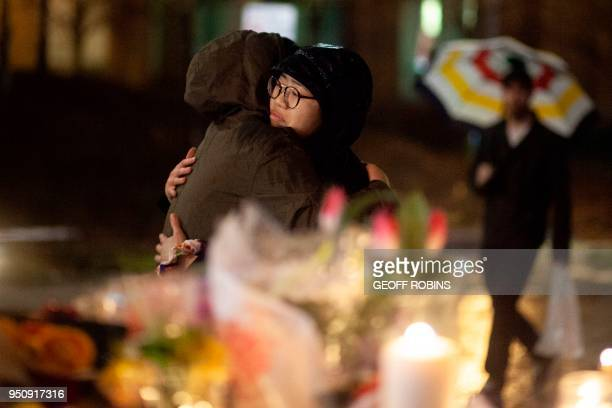Mourners share a hug during a candle light vigil near the site of the deadly van attack April 24 2018 in Toronto Ontario A van driver who ran over 10...
