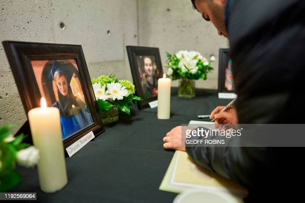 Mourners sign books of condolence at a memorial service at Western University in London Ontario on January 8 for 4 of the schools graduate students...