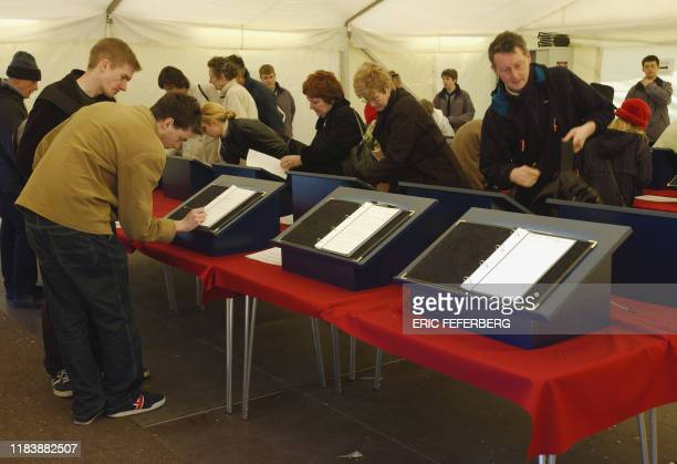 Mourners sign books of condolences to the queen mother on their way to Westminster Hall where her body liesinstate in London 06 April 2002 The queue...