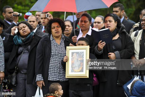 Mourners sing Fijian hymns and a boy holds a photograph of Private Ratu Silibaravi as they wait for the hearses carrying the coffins of Corporal...
