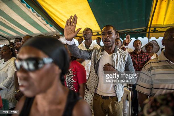 Mourners sing the national anthem as they pay their respects at an improvised altar for those who perished during the post electoral violence in...