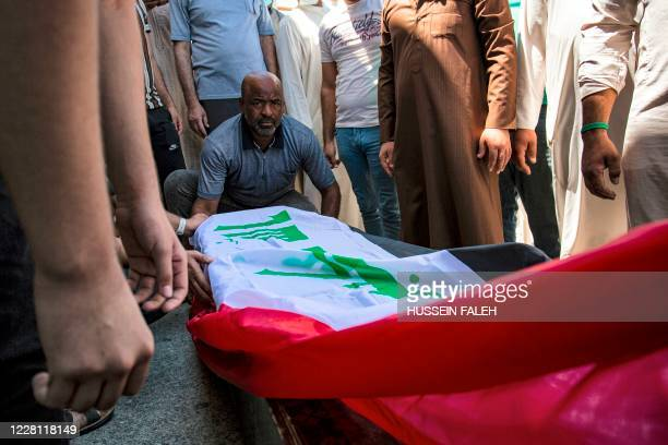 Mourners sit by the Iraqi-flag draped coffin of slain activist Riham Yaaqub during her funeral in the centre of Iraq's southern city of Basra on...