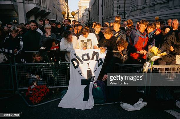 Mourners stand behind a temporary barricade outside Westminster Abbey on the day of Princess Diana's funeral just seven days after the tragic...