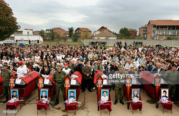 Mourners stand behind the coffins 06 October 2006 during a funeral ceremony of 13 Kosovo Albanians in Kosovo Polje Thirteen members of the Mirena and...