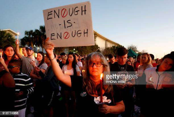 TOPSHOT Mourners stand during a candlelight vigil for the victims of Marjory Stoneman Douglas High School shooting in Parkland Florida on February 15...