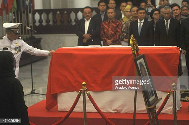 Mourners stand in one minute's silence in front of the coffin of Indonesian Ambassador of Pakistan Burhan Muhammad during a funeral ceremony in...
