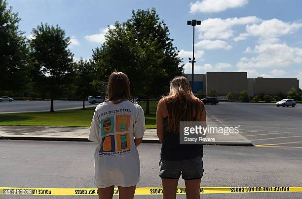 Mourners stand outside of the Grand Theatre on July 24, 2015 in Lafayette, Louisiana. Two People were killed and nine others wounded when a shooter...