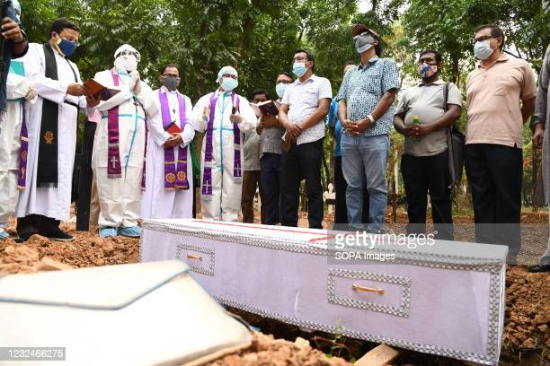 Mourners standing next to the coffin with the covid 19 deceased man, during a burial by Bangladeshi Christians at a cemetery.