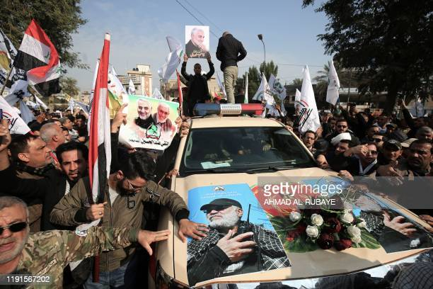 Mourners surround a car carrying the coffin of Iraqi paramilitary chief Abu Mahdi al-Muhandis during a funeral procession, for him and nine others,...