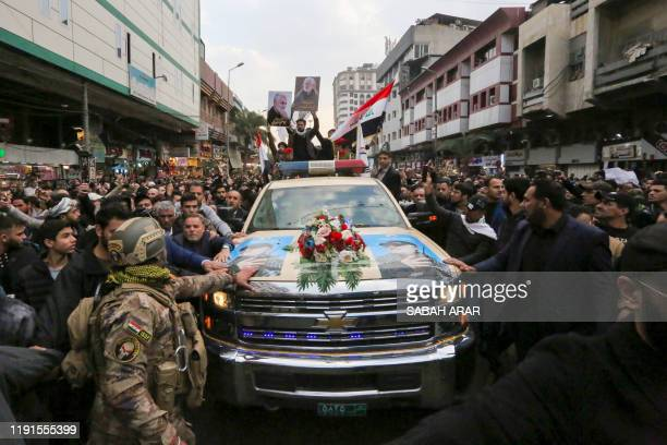 Mourners surround a car carrying the coffins of Iranian military commander Qasem Soleimani and Iraqi paramilitary chief Abu Mahdi alMuhandis killed...