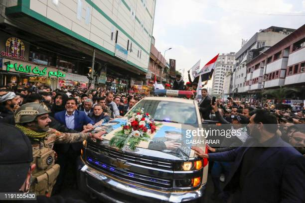TOPSHOT Mourners surround a car carrying the coffins of Iranian military commander Qasem Soleimani and Iraqi paramilitary chief Abu Mahdi alMuhandis...