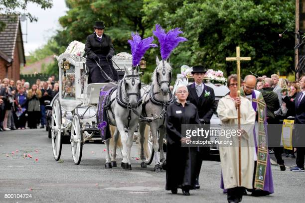 Mourners throw pink carnations as the funeral cortege of Manchester attack victim Lisa Lees leaves St Anne's Church on June 23 2017 in Oldham England...