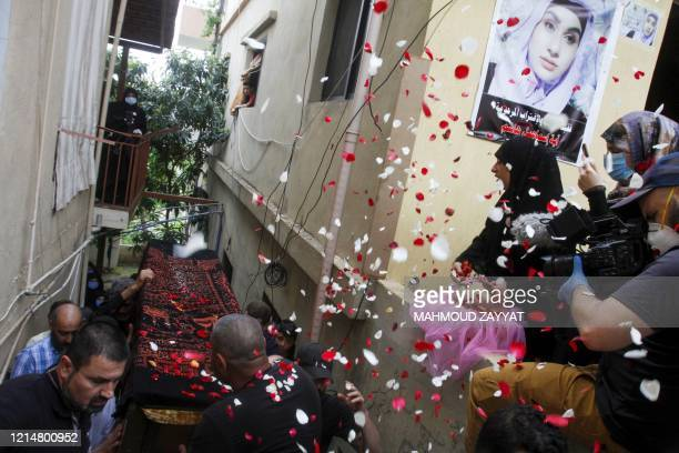 Mourners throw rose petals on the casket of Aya Hachem a 19yearold law student who was killed in a shooting in the UK town of Blackburn on May 17...