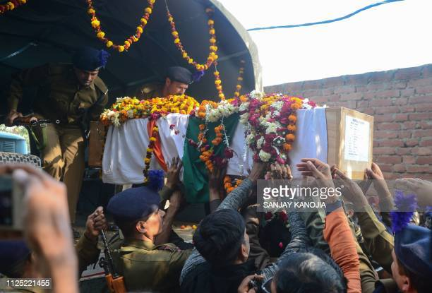 Mourners touch the coffin as they take part in the funeral procession for Indian Central Reserve Police Force trooper Mahesh Kumar Meena Meena at...